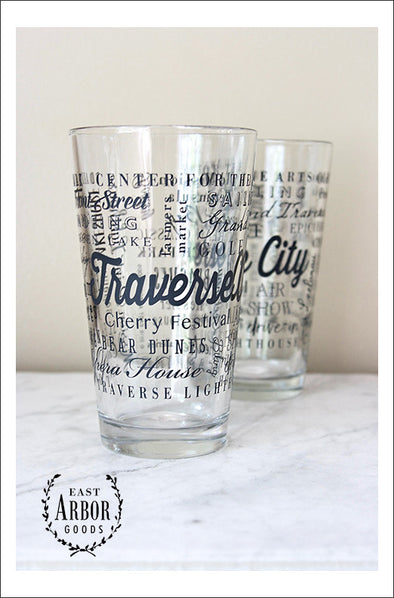 "Two clear pint glasses next to each other on a white marble countertop and against a white wall. Glass design is made up of words in black screen print in different fonts and sizes with the words ""Traverse City"" the largest and centered and the other words wrapping around the glasses."