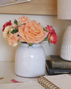 Close up of a medium-size white painted pottery vase filled with peach and pink roses and carnations on a home office desk.