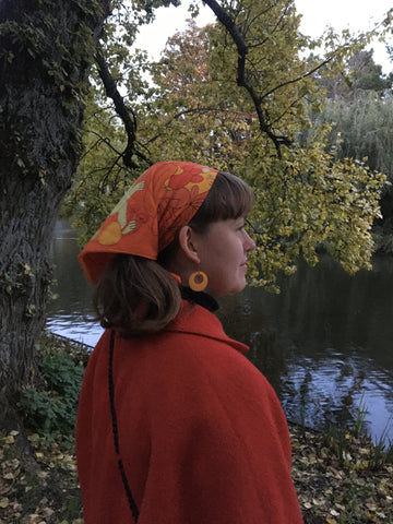 Faith looking out towards a river wearing an orange headscarf