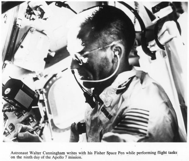 Astronaut Walter Canningham writes with his Fisher Space Pen while performing flight tasks on the ninth day of the Apollo 7 mission.