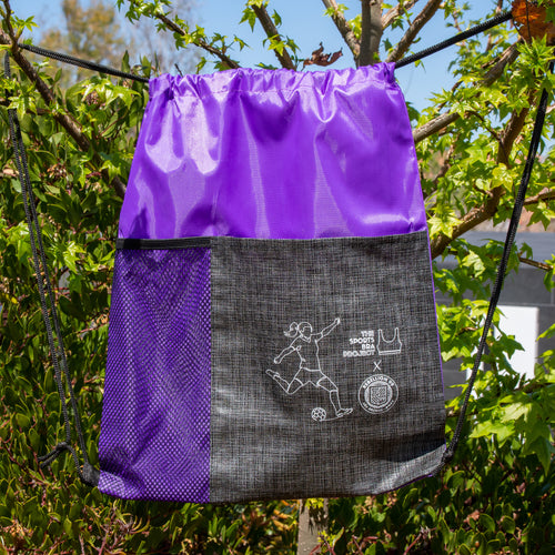 Purple drawstring backpack is shown in front of green trees.