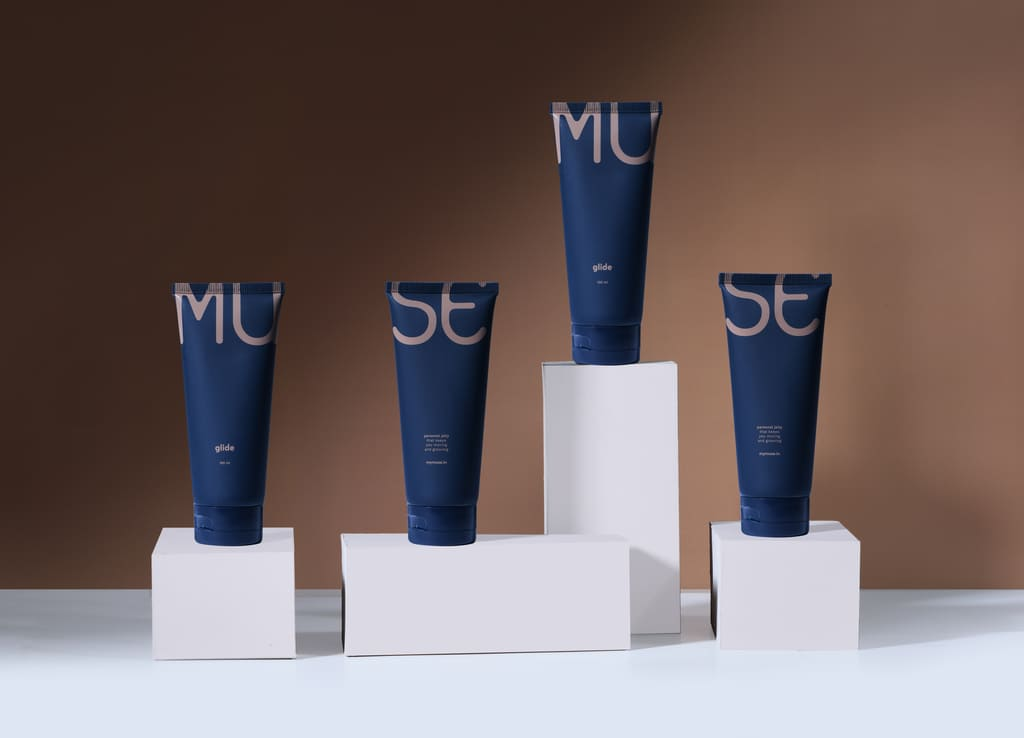 Four 100ml Glide personal jelly tubes (Dark Blue) placed on white blocks