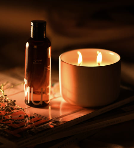 The Mood Setter Kit by MyMuse featuring 100ml Glow relaxing oil placed on a magazine next to a lit dual wick Spark candle