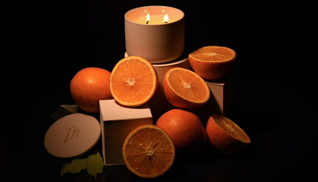 Burning Spark Bergamot Mahogany candle placed on blocks with sliced oranges spread around in a dark-lit room