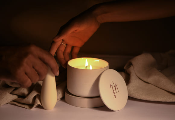 Pulse handheld massager by MyMuse being used on a persons legs in bed against white sheets with a beautiful shadow