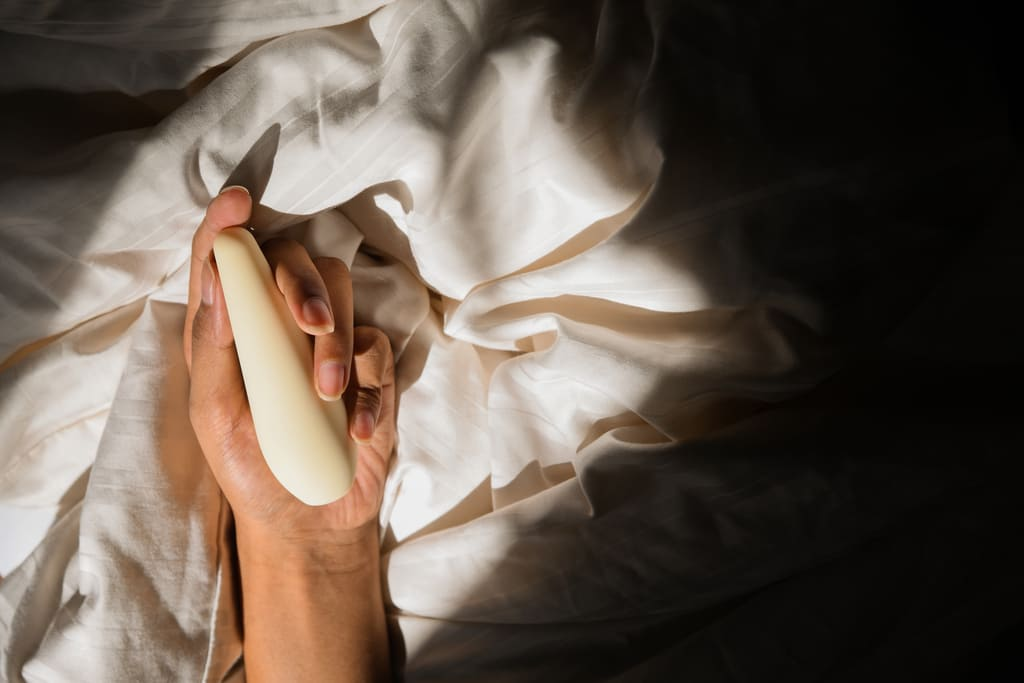 Hand holding Pulse, a full body massager, while lying down on the bed with white blankets and a dark shadow on the right