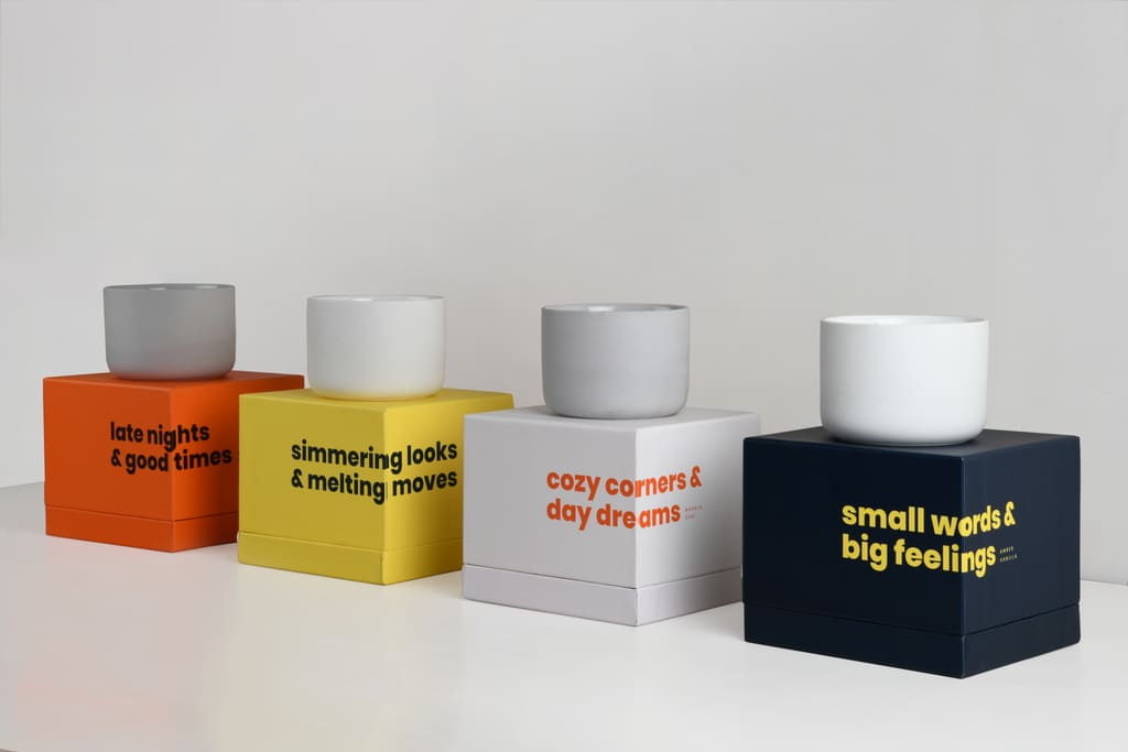 Four different scented Spark candles resting on their respective boxes in a straight line (white background)