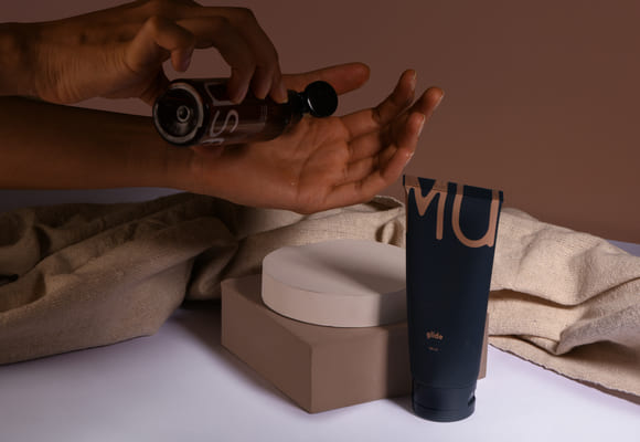 100ml Glow relaxing bottle and 100ml Glide personal jelly, or the Slip and Slide kit by MyMuse, placed in a marble tray in a dimly-lit bathroom