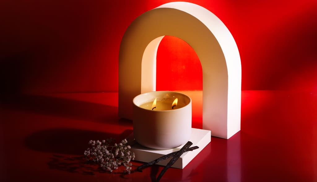 Burning Spark Amber Vanilla candle with flowers and a U-shaped ceramic artifact set against a red background