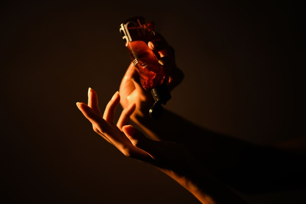 A person applying Glow Arousing massage oil directly on their hands in a dark-lit room