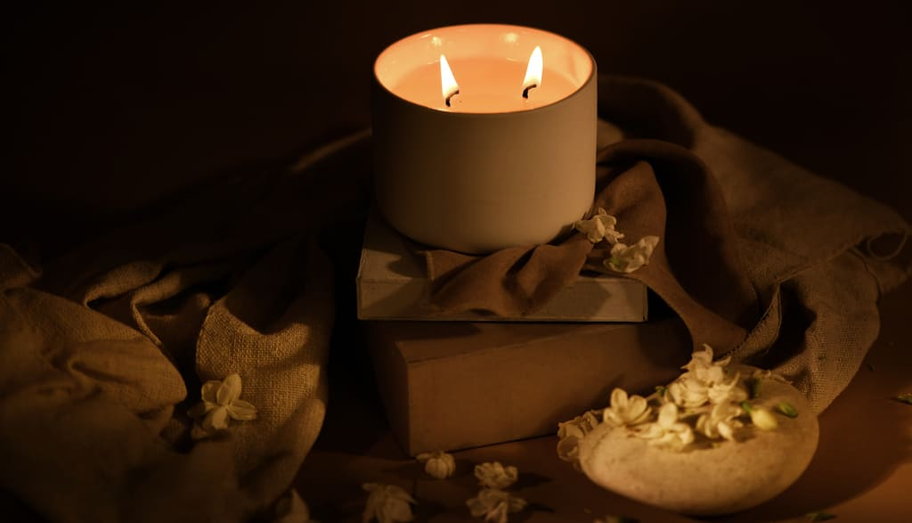 Burning Spark Jasmine Ylang candle placed on two wooden blocks with Jasmine flowers spread around in a dark-lit room