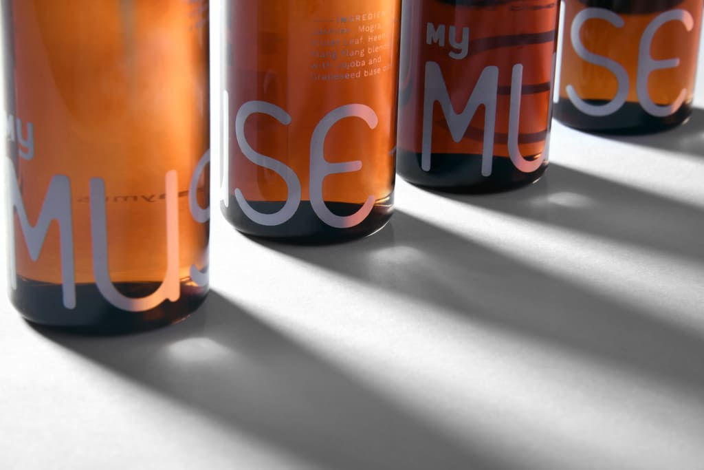 Bottom of four 100ml Glow Arousing massage oil bottles kept in a straight line forming their shadows