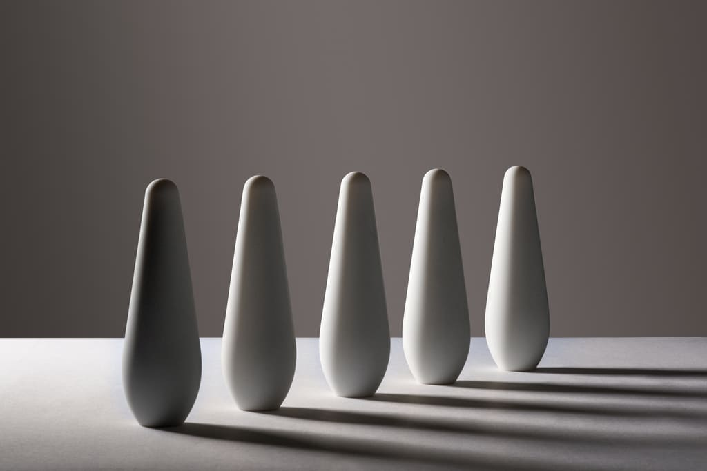 Five Pulse massagers standing upright in a line with a dark grey background forming shadows due to the falling light