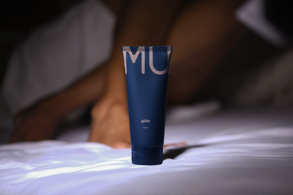 MyMuse 100ml Glide personal Jelly standing on a bed with legs in the background