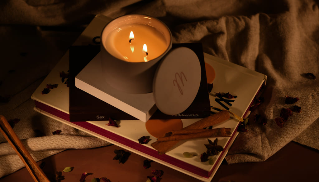 Burning Spark Masala Chai candle placed on books with its lid on the side in a dark-lit room
