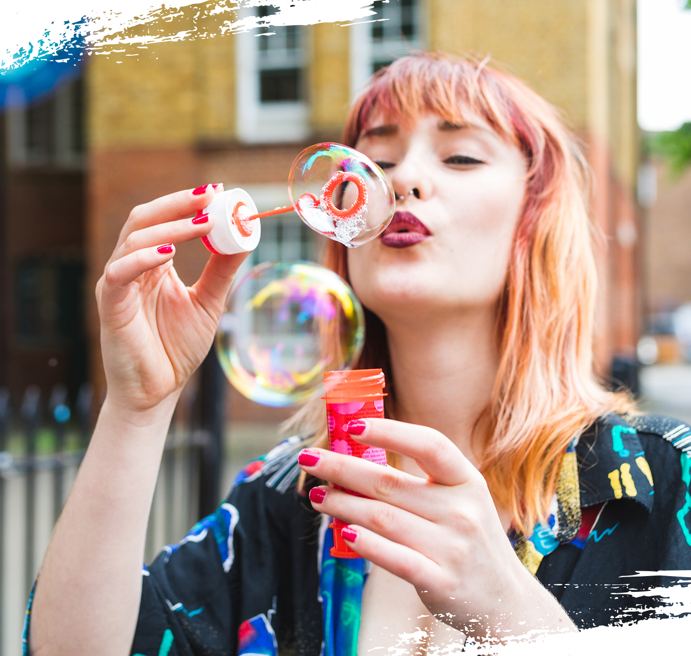 Image of woman with coloured hair blowing bubbles