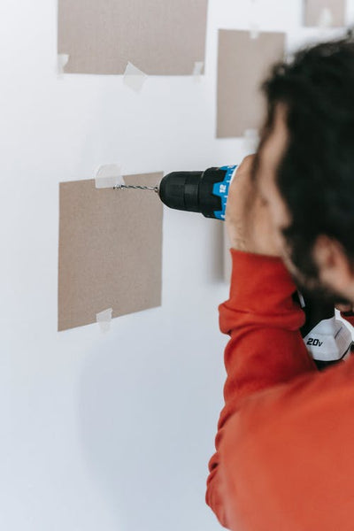 someone drilling a hole on the wall
