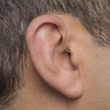 A person's ear with Phonak Audeo 50 / 90 hearing aids with invisible dome