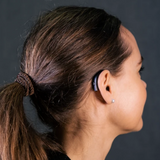 A woman is wearing a discreet Behind the Ear ReSound ONE 5/9  hearing aid
