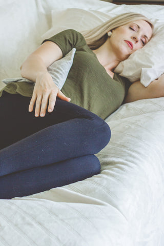 Woman lying down with heating pad