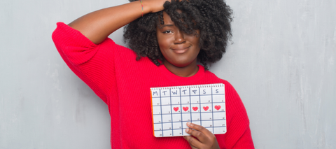 Woman in red shirt holding calendar showing when her menstrual cycle will be