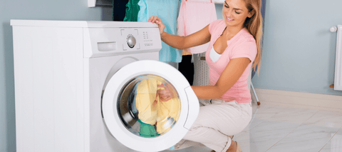 woman in pink shirt beside washer
