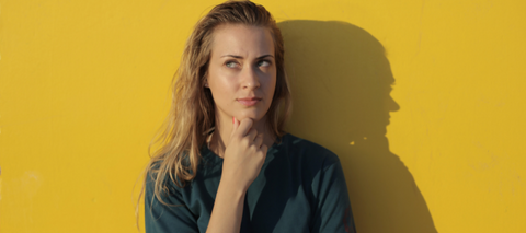 Woman thinking against yellow background