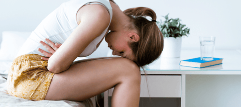 Woman hunched over in pain from cramps