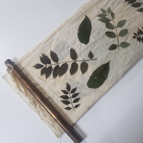 leaves on fabric with a copper pipe to bundle around