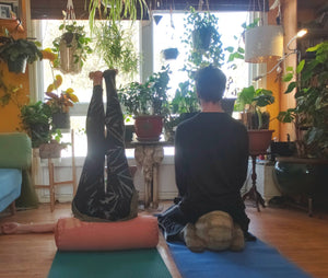 yoga props a man on the right siting on his knees with a pillow under him. A set of legs on the left up in the air supported by a yoga bolster