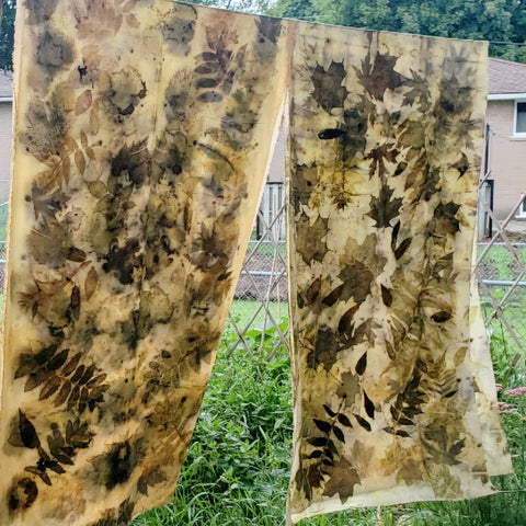 plant dyed fabric , prints of leaves all over it hanging on a line