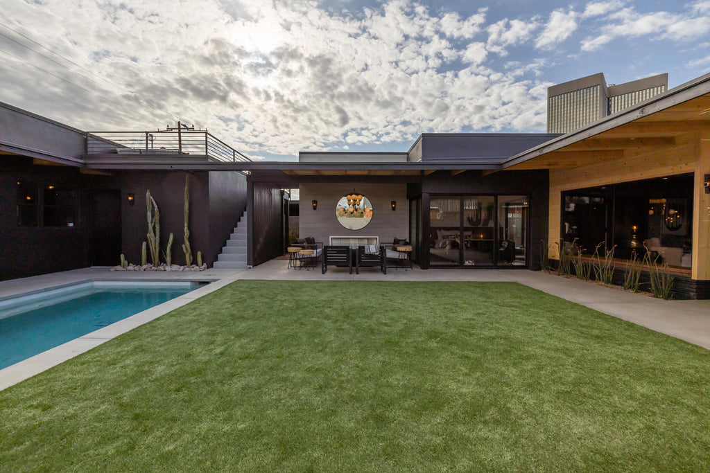 James Judge woodward outdoor transformation showing a grassy area, pool, and outdoor fireplace with black furniture and a grey board-formed concrete feature wall