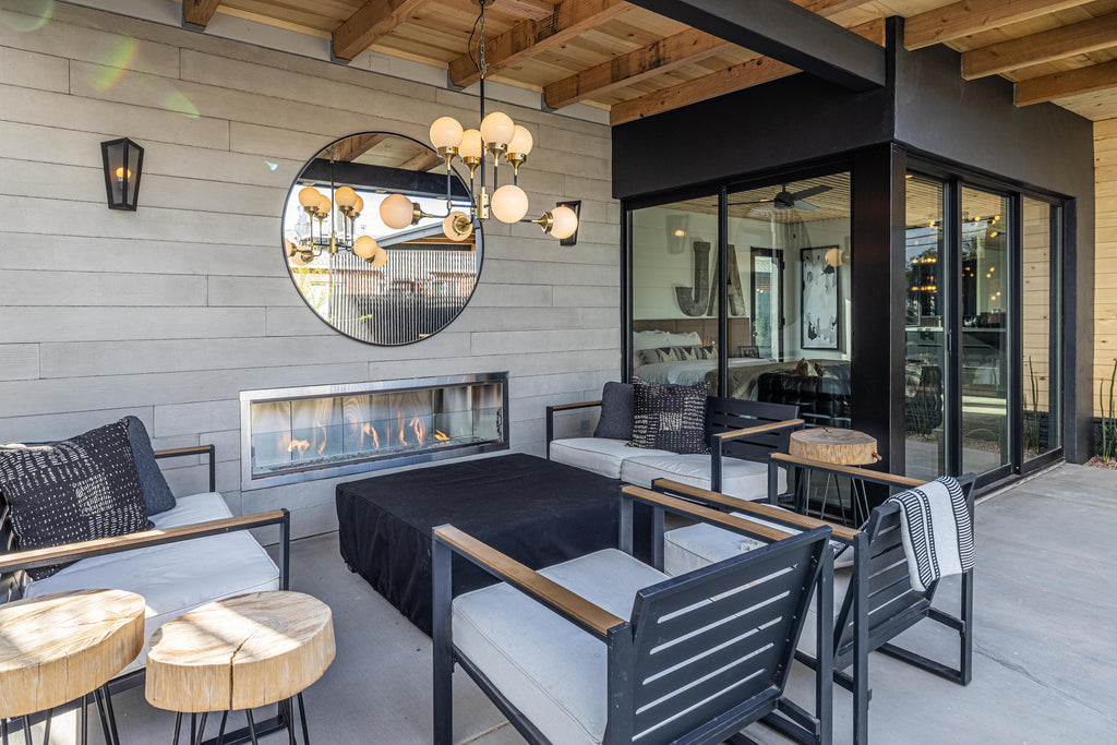 James Judge Outdoor Fireplace surrounded with Wall Theory RealCast Board-form concrete panels, with grey and black outdoor furniture and mirror and light fixture in the centre