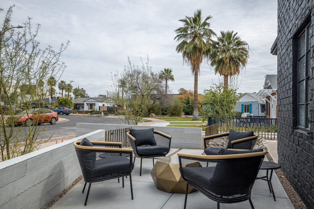 James Judge courthard featuring black outdoor furniture and a bronze angular outdoor table and concrete board formed panels
