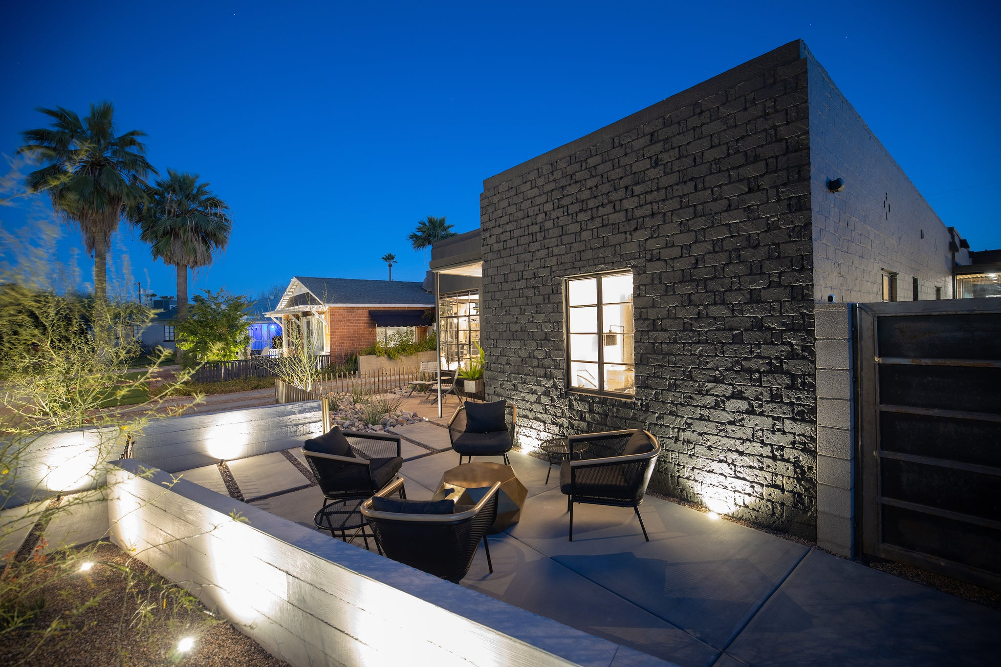JAmes judge home exterior showing courtyard with board-formed concrete panels on the half wall and black outdoor furniture