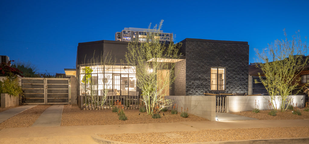 James Judge Arizona home renovation showing the black exterior of the house and a large angled window, with metal driveway gate