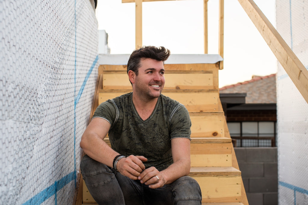 James Judge wearing a green t-shirt sitting on wood stairs beside a white fence