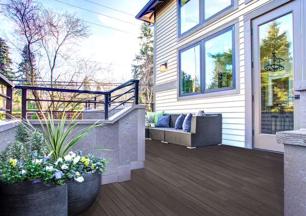 LANAI Premium Plank Decking in Sunset Palm on a deck in front of a white house with potted plants on the deck.