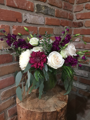 Soft green eucalyptus drapes over a clear glass vase. Deep purple stocks and creamy Playa Blanca roses are the stars of this garden style arrangement  complemented by long lasting cremons and lisianthus   Available for delivery in Kenora