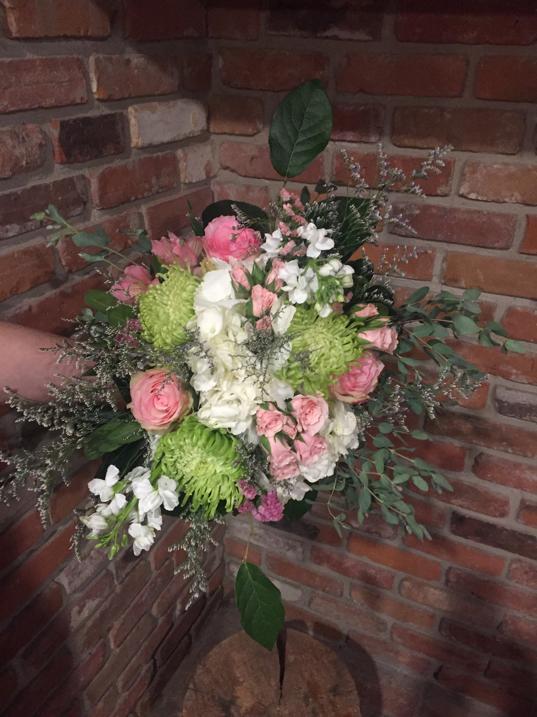 A gorgeous collection of sweet scented florals in a soft palette of white, pink and green skirted with premium foliages. Includes jumbo white hydrangea, pink roses, pink spray roses, white stocks, green spider mums, lavender limonium and pink statice. Hand tied and ready for your recipient to drop into her vase! Sure to take her breath away!