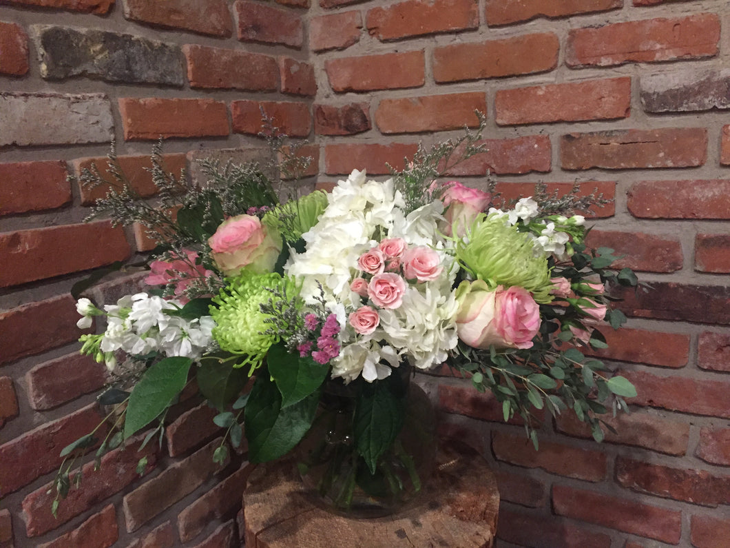 A show stopping 360 degree collection of sweet scented florals in a soft palette of white, pink and green skirted with premium foliages is an upgraded vase she'll be happy to add to her collection! Sure to take her breath away! Includes jumbo white hydrangeas, green spider mums, light pink spray roses, light pink Esperance roses, light pink alstromeria, fragrant white stocks, lavender limonium, pink statice skirted with draping gunny eucalyptus and salal