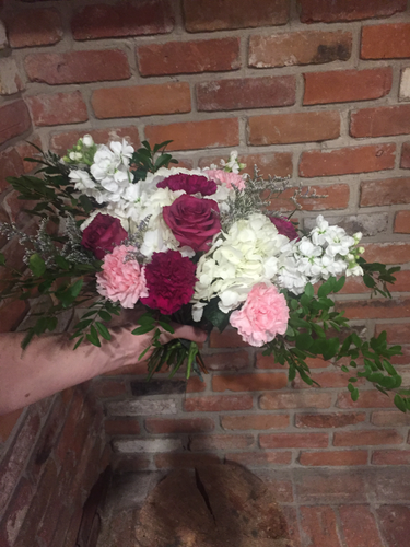 A beautiful garden style hand tied bouquet including a jumbo white hydgrangea, fragrant white stocks, blueberry roses and plum and light pink carnations. A touch of whispy lavender limonium and an assortment of foliages add loads of texture! Arranged and ready for your recipient to drop in their vase