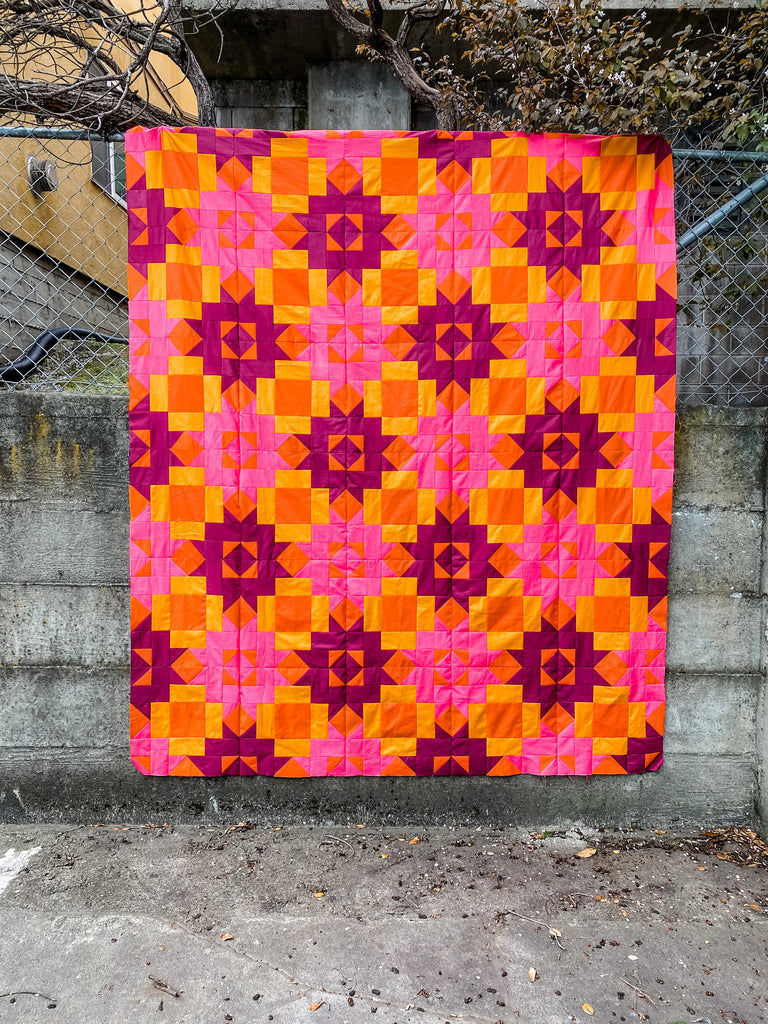 Petal Points quilt top in pink and orange.