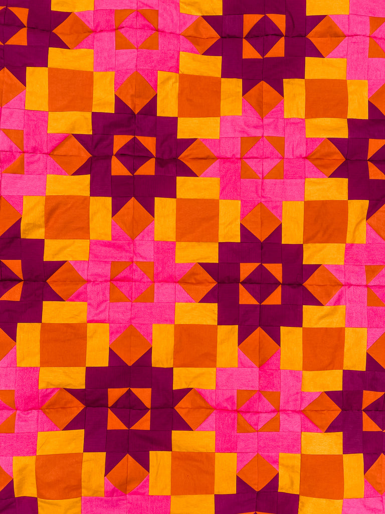 Flat quilt top in pink and orange - Petal Points quilt pattern
