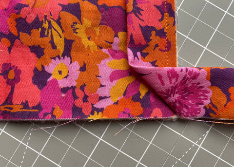 Pull binding away from the corner, creating a 45 degree fold.
