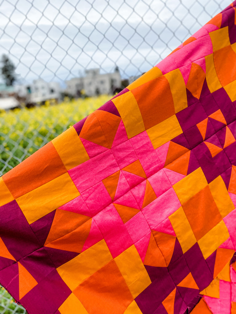 Pink and orange quilt top against a chain link fence, surrounded by a field of yellow flowers.