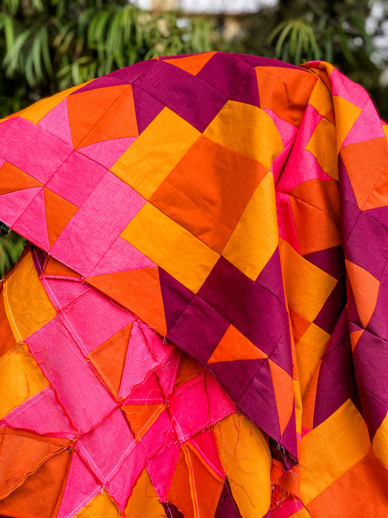 Quilt top in hot pink, wine, rust and bright orange.