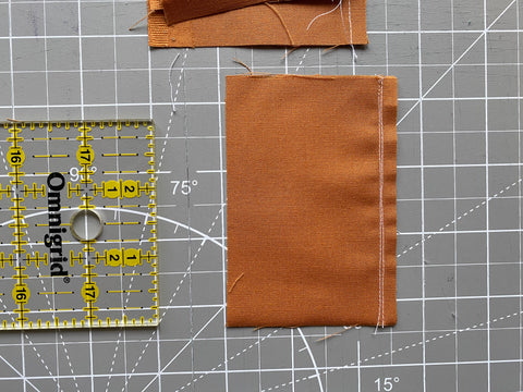 """Fabric on cutting mat with regular and scant 1/4"""" seam sewn."""