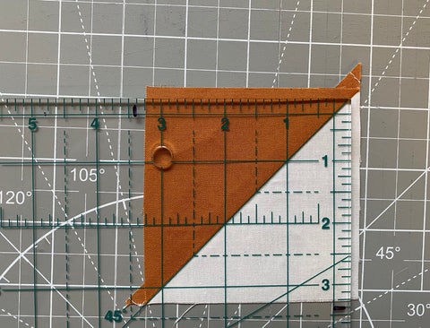 Lining up a square ruler over a HST block