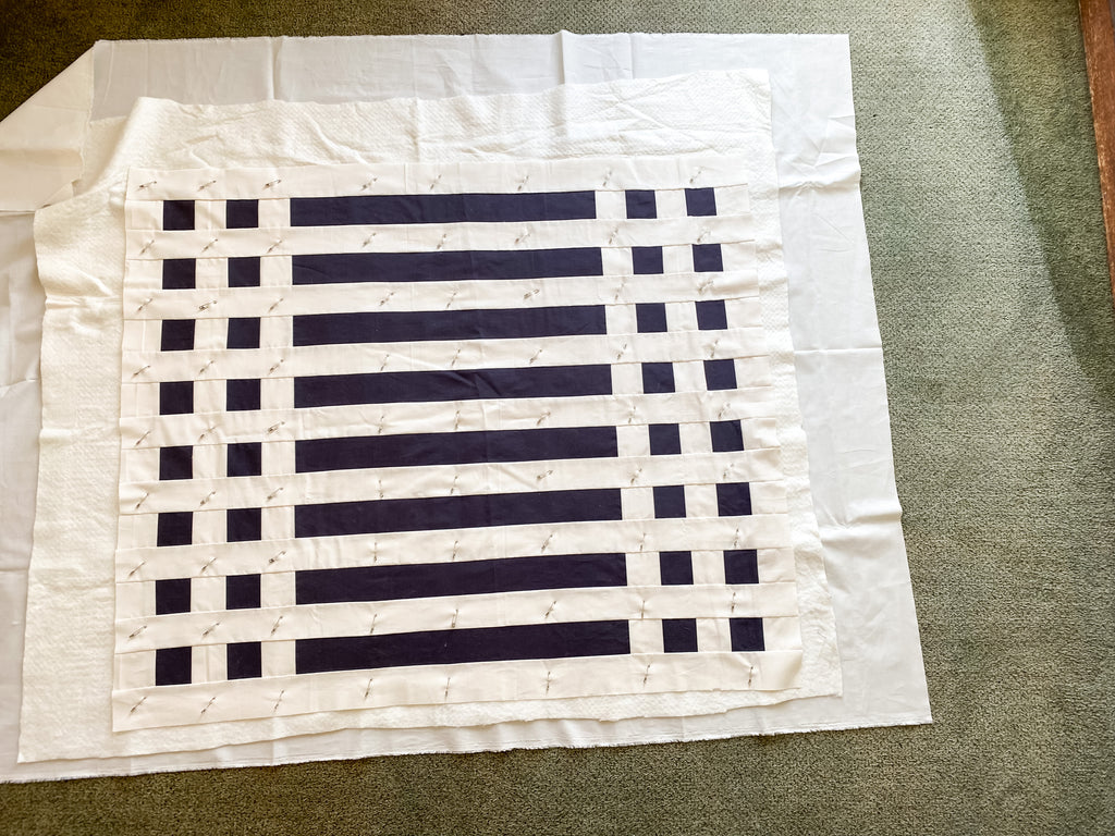 how to baste a quilt - simple stripes quilt - fully basted quilt on the floor